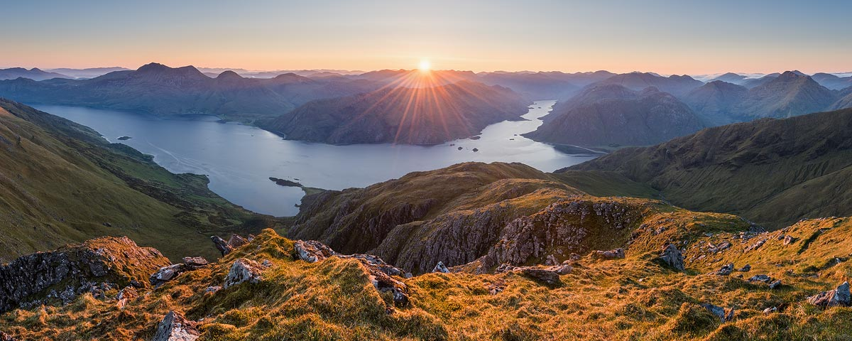 A panoramic view of Loch Hourn as the sun appears over the horizon