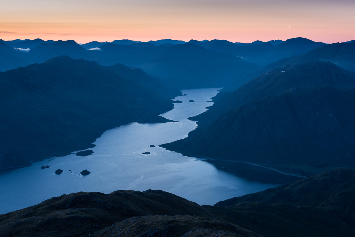 Blue hues of dawn as the moon sets over the Knoydart